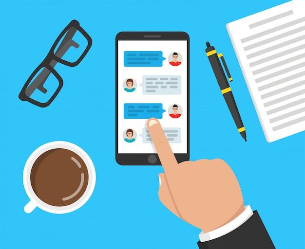 Hand met telefoon met berichten op het scherm