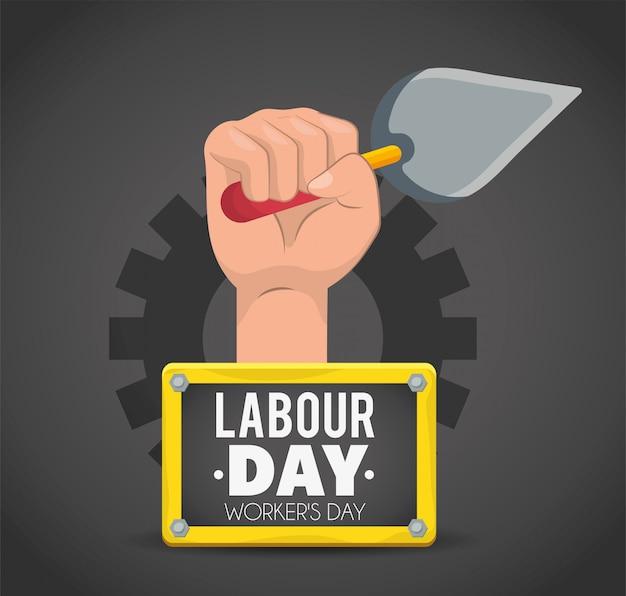 Hand met troffel en embleem aan arbeidsdag