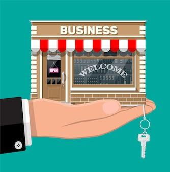 Hand met winkel of commercieel onroerend goed met sleutel. promotie van onroerend goed, opstarten. nieuw bedrijf verkopen of kopen. kleine europese stijl winkel buitenkant. platte vectorillustratie