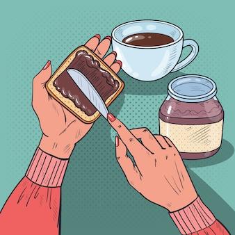 Handen die chocoladeroom op de plak van het brood verspreiden