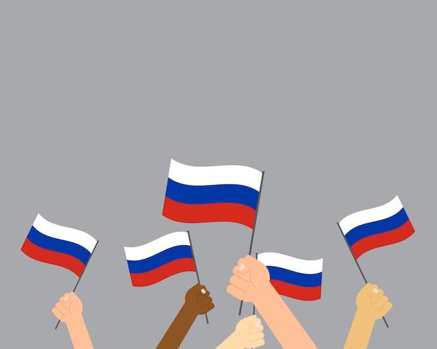 Handen die de vlaggen van rusland houden die op grijze achtergrond worden geïsoleerd