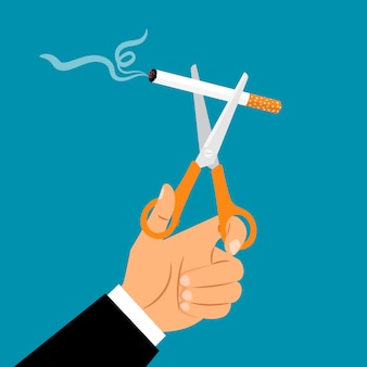 Handen die schaar snijdende sigaret houden