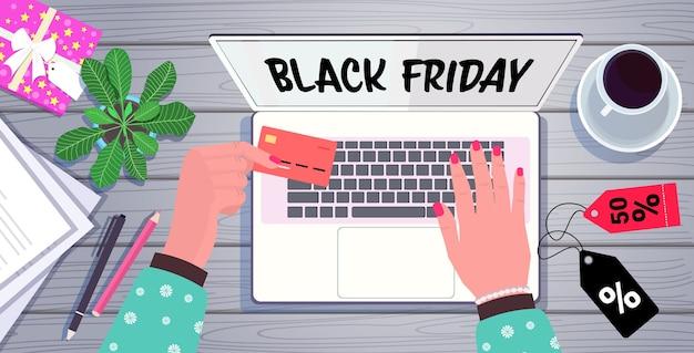 Handen met behulp van laptop online winkelen zwarte vrijdag verkoop vakantie kortingen e-commerce concept werkplek desk top angle view