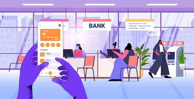 Handen met behulp van mobiel bankieren app met creditcard op smartphone scherm e-betalingen financiële applicatie