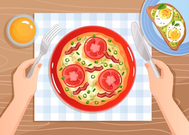 Handen met bestek over roerei met tomaten en spek op houten tafel plat