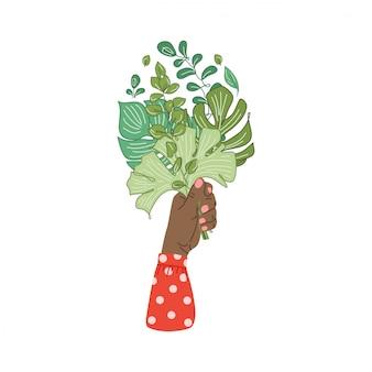 Handen met boeket samenstelling van takken van tropische planten, bladeren. vrouwelijke hand met bloemen. bloemen decoratief ontwerpelement dat op wit wordt geïsoleerd