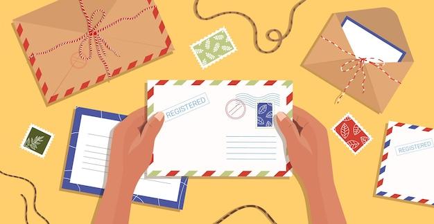 Handen met een envelop. brieven, ansichtkaarten en enveloppen liggen op tafel