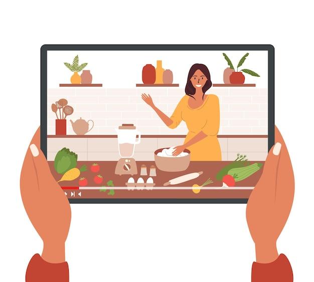 Handen met een tablet met een kookblog of een online les.