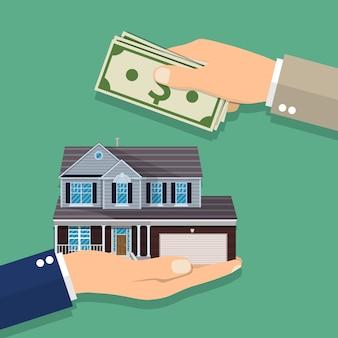 Handen met geld en huis.