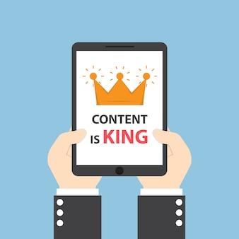 Handen met tablet met woorden inhoud is koning