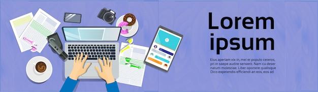 Handen typen op laptopcomputer, bovenaanzicht op bureau met digitale tablet en slimme telefoon werkplek
