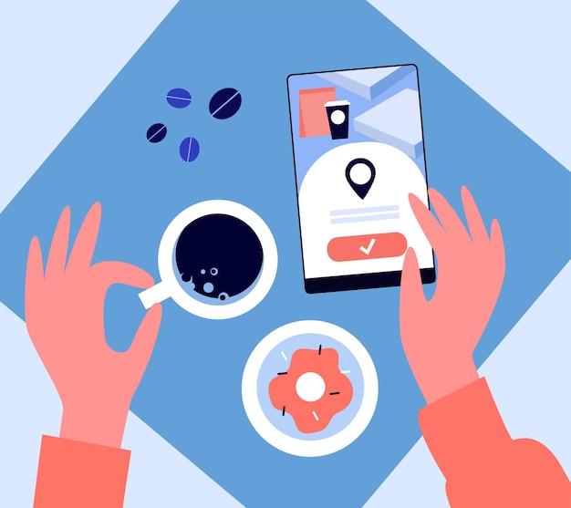 Handen van vrouw met behulp van mobiele telefoon in coffeeshop