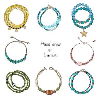 Handgetekende set sieraden armbanden aan de hand.