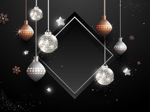 Hangende kerstballen met sterren en sneeuwvlokken versierd op zwart met leeg frame copyspace