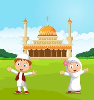 Happy cartoon islamitische kinderen zwaaien hand voor moskee