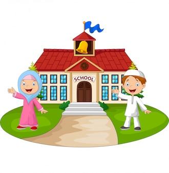 Happy cartoon moslim kinderen voor schoolgebouw zwaaiende hand
