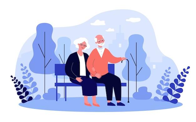 Happy senior paar ontspannen in het park, zittend op een bankje, hand in hand. oude man met stok en vrouw genieten van vrije tijd buitenshuis. voor oudere leeftijd, pensioen, relatieconcept