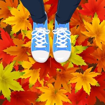 Herfstbladeren achtergrond sjabloon met esdoorn bladeren benen bovenaanzicht in schoenen sneakers op kleurrijke vallende bladeren.