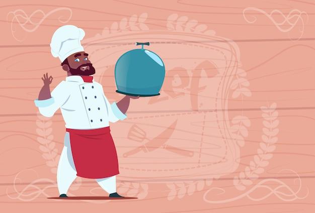Het afrikaanse amerikaanse kok van de chef-kokholding dienblad met schotel het glimlachen beeldverhaal in wit restaurant eenvormig over houten geweven achtergrond
