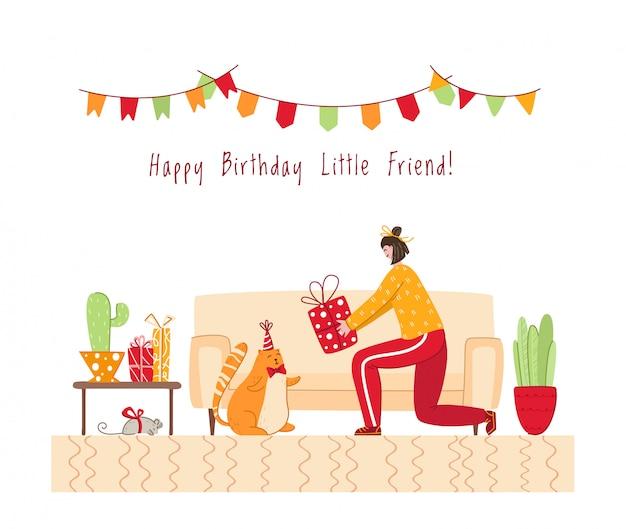 Het concept van de huisdierenverjaardag - het meisje geeft giftdoos aan rode kat in feestelijke hoed, gezellig ruimtebinnenland met vakantiedecoratie