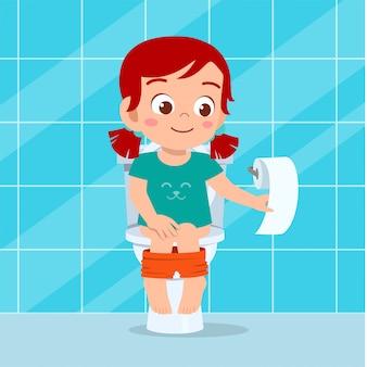 Het gelukkige leuke jong geitjemeisje zit op het toilet