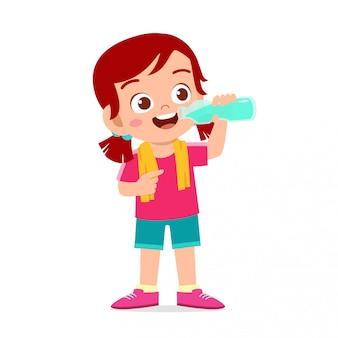 Het gelukkige leuke jonge geitjemeisje drinkt water na sport