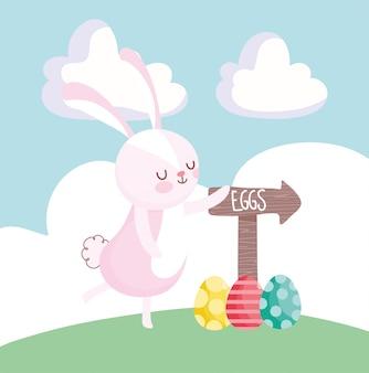 Het gelukkige leuke konijn van pasen met eieren en pijl op gras