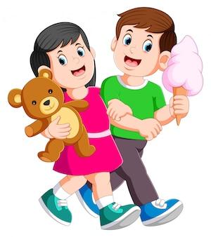 Het jonge paar brengt romantisch door terwijl de dame teddybeer in handen houdt