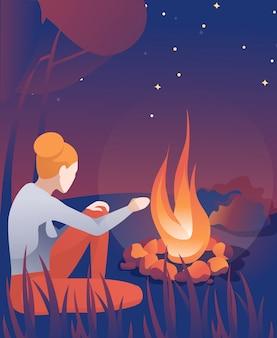 Het jonge vrouw verwarmen overhandigt dichtbij vreugdevuur bij nacht