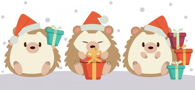 Het karakter van schattige egel zittend op de grond en met een geschenkdoos in het winterseizoen.