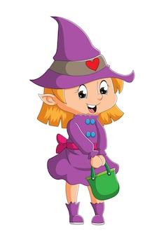Het kleine heksenmeisje staat met een felgroene mand met illustratie