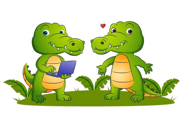 Het koppel van de slimme krokodil houdt de nieuwe laptop vast in de illustratietuin