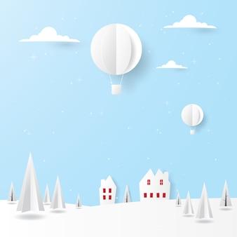 Het landschap van de landschapswinter, huizen, pijnboombomen en hete luchtballon die in de hemel vliegen
