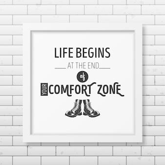 Het leven begint aan het einde van je comfortzone - citeer typografische achtergrond in het realistische vierkante witte frame op de bakstenen muurachtergrond.