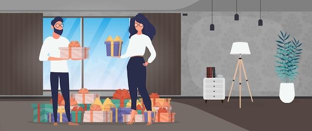 Het meisje en de jongen houden geschenken in hun handen. vrouw en man met geschenken in hun handen. vakantieconcept. vector.