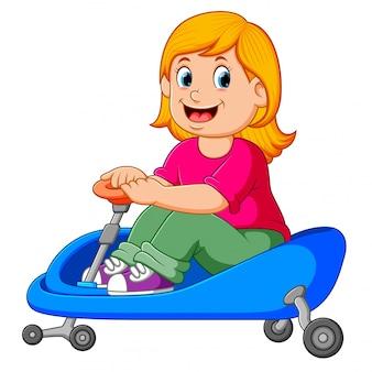 Het meisje fietst op de blauwe driewieler