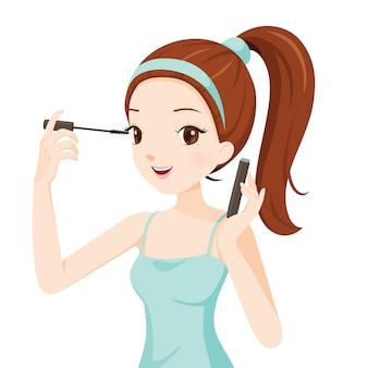 Het meisje make-up haar ogen met mascara