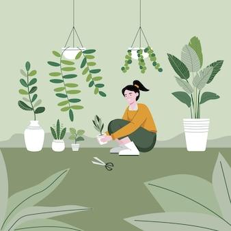 Het meisje plant met zorg bomen in de tuin.