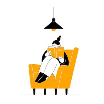 Het meisje zit in een fauteuil en leest een boek