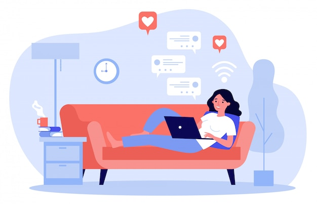 Het mooie vrouw ontspannen bij bank met laptop computer