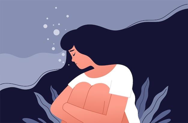 Het ongelukkige meisje zit en knuffelt haar knieën in een zee van haar eigen verdriet
