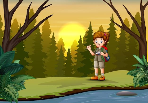 Het ontdekkingsreizigersmeisje met haar camera in bos