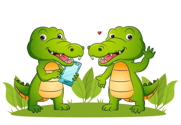 Het paar gelukkige krokodillen houdt een smartphone ter illustratie vast
