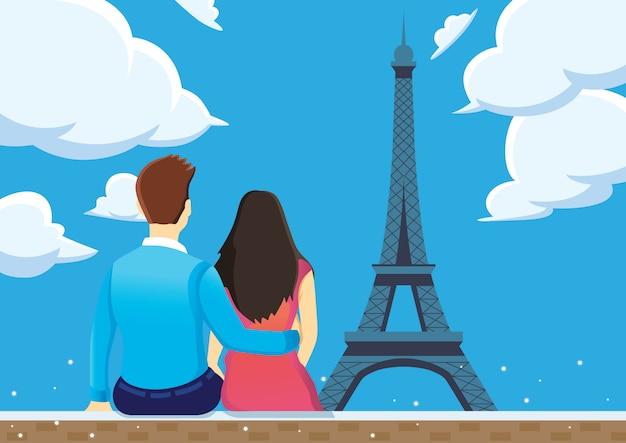 Het paar geniet van dichtbij de toren van eiffel met blauwe hemel.