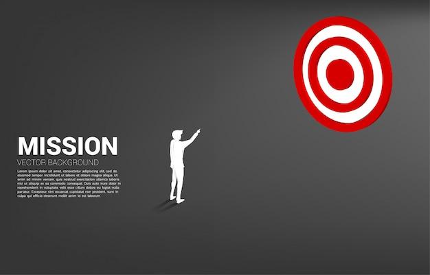 Het punt van de silhouetzakenman op centrum van dartboard. businessconcept van marketing doelgroep en klant