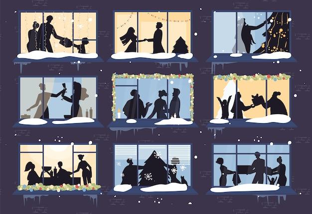 Het raam van het avondkerstmis toont gelukkige familie