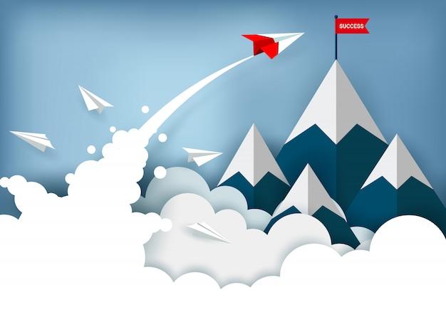 Het rode papieren vliegtuig vliegt naar het rode vlagdoel op bergen terwijl het boven een wolk vliegt