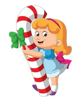 Het schattige meisje houdt een grote snoepstok met illustratie vast