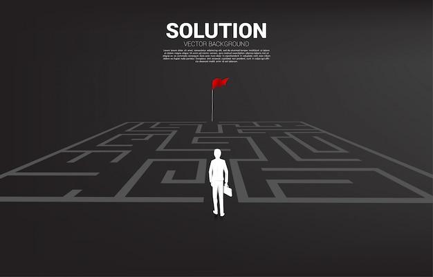 Het silhouet van zakenman gaat binnen om aan rode vlag te doolhof. bedrijfsconcept voor het vinden van een oplossing en het bereiken van het doel