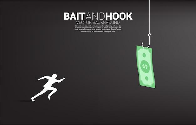 Het silhouet van zakenman het lopen volgt bankbiljet met visserijhaak. concept aas en haak in zaken.